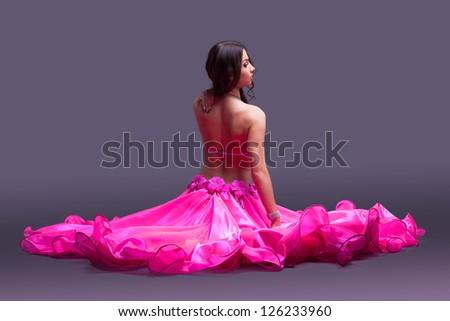 Dancer in pink costume sitting on floor - stock photo