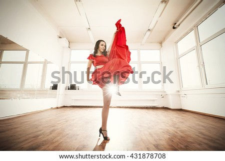 dancer in red dress rehearsing her performance in studio - stock photo