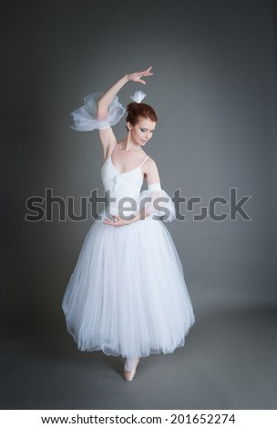 dancer in the white tutu dancing on a grey background