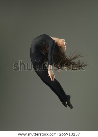 dancer performing high jump and backbend against grey background