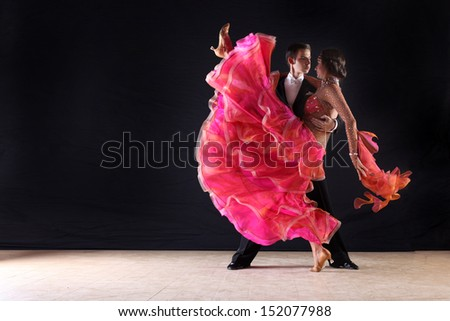Dancers in ballroom against black background - stock photo