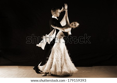 dancers in ballroom against on black
