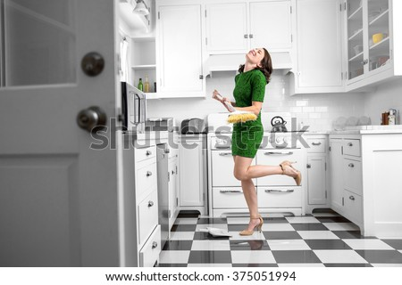 Dancing and singing while cleaning sweeping kitchen floor fun spirited joyful attitude chores - stock photo