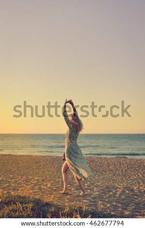 Dancing beautiful female walking on the beach wearing long dress, outdoors dawn sky  background