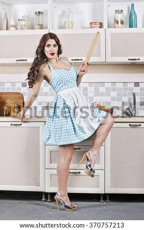 dancing beautiful girl with rolling pin in a hand,in the kitchen