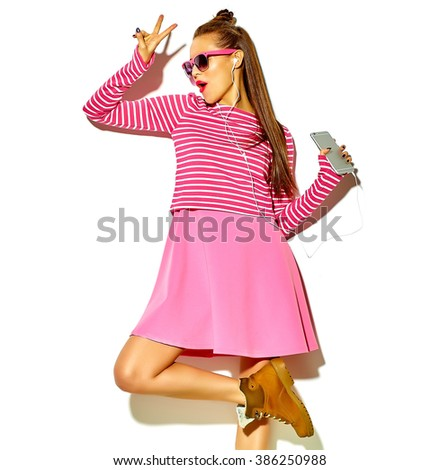 dancing beautiful happy cute smiling sexy brunette woman girl in casual colorful pink summer clothes with red lips isolated on white listening to music and showing peace sign - stock photo