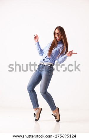dancing cheerful beautiful business woman, isolated over light grey studio background