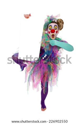 Dancing Clown holding a placard in the hand and pointing at it - stock photo