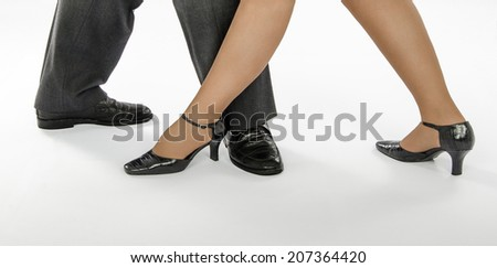 Dancing couple in crocodile shoes showing tango step on white background - stock photo