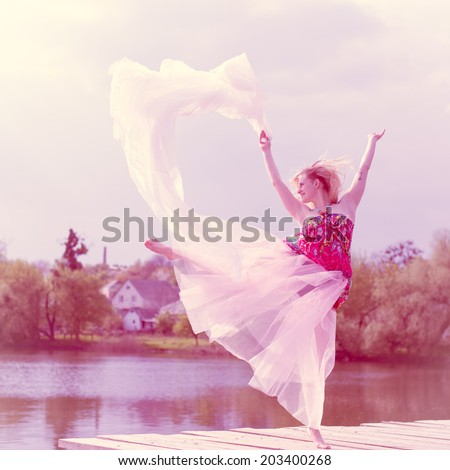 dancing in white skirt beautiful blond young woman with falling sun light rays from sky at river or water lake on spring or summer nature green outdoors background copy space portrait image - stock photo