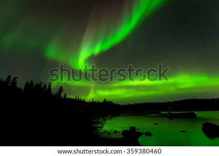 Dancing Lights - Colorful northern lights appear over evergreen forest surrounding a lake.  - stock photo