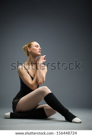 Dancing on the floor ballerina with her eyes closed, isolated on a white on grey. Concept of elegant art and sportive hobby - stock photo