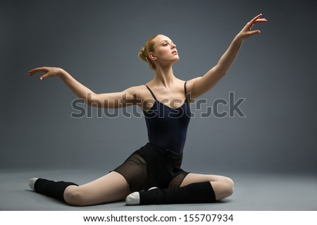 Dancing on the floor ballerina with her hand up, isolated on white on grey. Concept of elegant art and sportive hobby - stock photo