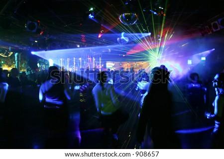 Dancing people between scanner/laser light in a disco - stock photo