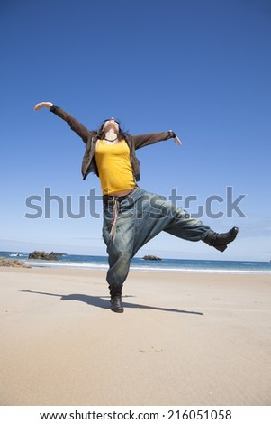 dancing pregnant woman with yellow shirt at Asturian beach - stock photo