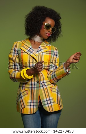 Dancing retro 70s fashion african woman with sunglasses. Yellow jacket and green background.