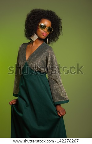 Dancing retro 70s fashion afro woman with green dress and sunglasses. Green background.