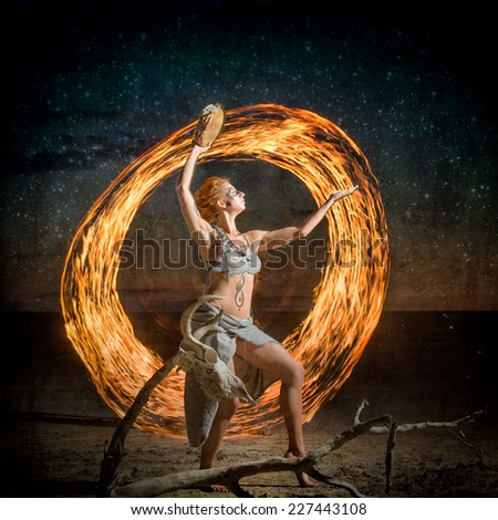 Dancing shaman. Portrait of a body painted girl dancing with the flame - stock photo