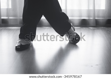 Dancing shoes feet and legs of male ballroom and latin salsa dancer dance teacher in dance school rehearsal room class.