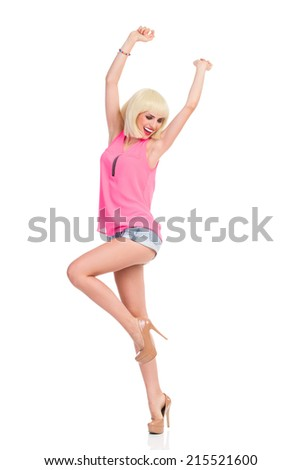 Dancing slim girl. Smiling blond young woman in high heels and pink top dancing on one leg with arms raised. Full length studio shot isolated on white. - stock photo