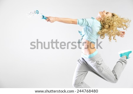 Dancing woman holding paint roller - stock photo