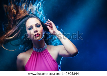 dancing woman in pink dress and  hair in motion   studio shot - stock photo