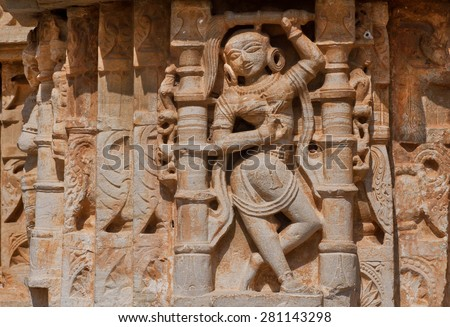 Dancing woman in traditional indian position on the historical carved stone wall of hindu temple, India - stock photo