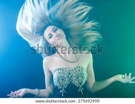 Dancing young woman over bright green and blue lights - stock photo