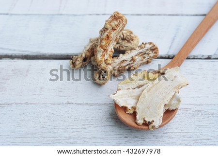 dang gui (angelica sinensis) and dang gui ginseng slice on wooden spoon, traditional chinese herbal medicine. - stock photo