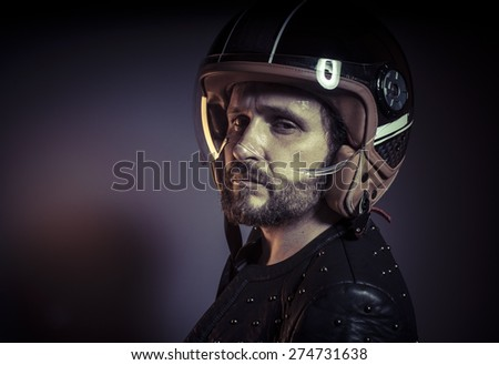 Danger, biker with motorcycle helmet and black leather jacket, metal studs - stock photo