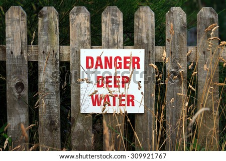 Danger Deep Water sign fitted to wooden fence