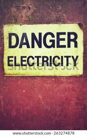 Danger electricity warning sign on old rusty metal plate, box. - stock photo