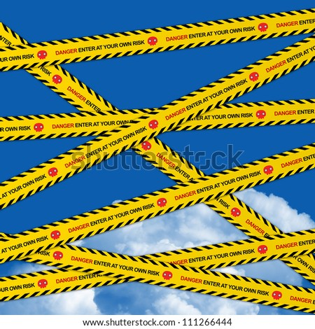 Danger Enter At Your Own Risk Caution Tape in Blue Sky Background - stock photo