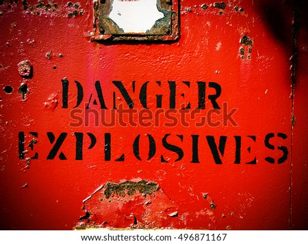 Danger explosives weathered bright red sign