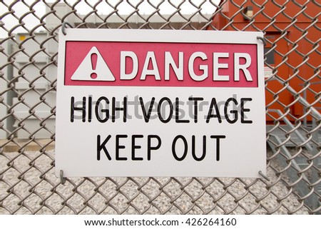 Danger high voltage keep out sign on chain link fence. - stock photo