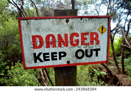 Danger keep out wooden sign panel posted in the wilderness. concept photo of travel and outdoor activity. - stock photo