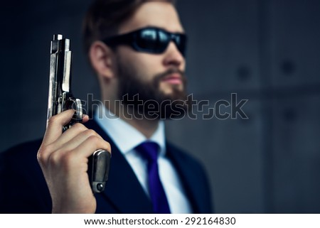 Danger man agent with gun and sunglasses. Focus on gun. - stock photo