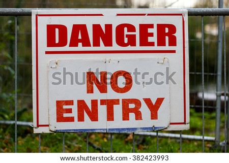 Danger no entry warning board on fence
