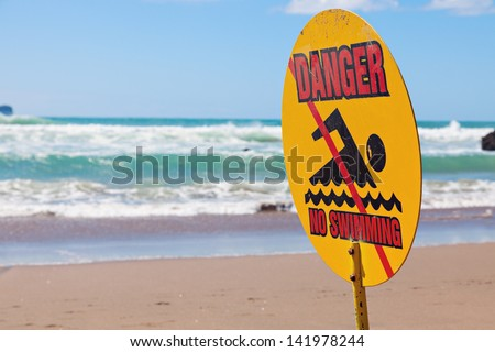 Danger - no swimming. Sign seen on the beach in New Zealand. - stock photo