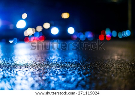 Danger of the city at night, the cars driving on the road and shine the headlights. View from the level of asphalt, in blue tones - stock photo