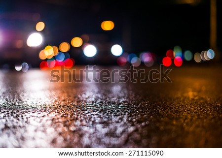 Danger of the city at night, the cars driving on the road and shine the headlights. View from the level of asphalt - stock photo