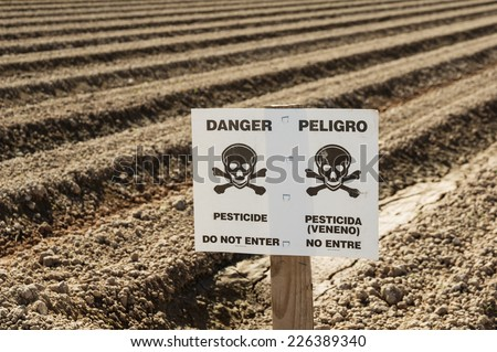danger pesticide sign in field ready for planting - stock photo