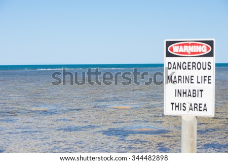 Danger Sign, caution symbol at coastal reef warning of harmful marine life in ocean, with panoramic seascape, summer sunny blue sky, horizon, copy space. - stock photo