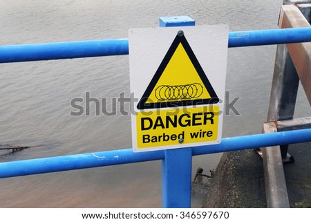 Danger sign for barbed ire security fence.