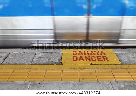 Danger sign in Malay & English language on a train platform with a zooming arrival train.  - stock photo