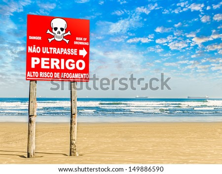 """Danger sign on a paradise beach in Brazil on summer. It is in portuguese, written """"Danger, no trespassing"""". - stock photo"""
