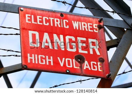 Danger Sign on a powerline tower warning of High Voltage - stock photo