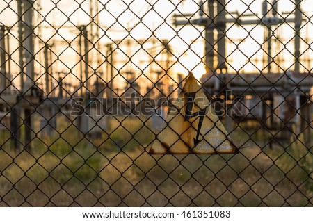 Danger sign on the fence on the background electrical substation