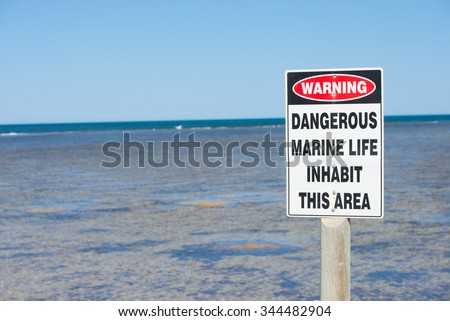 Danger Sign symbol at coastal reef warning of harmful marine life in ocean, with panoramic seascape, summer sunny blue sky, horizon, copy space.