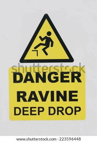 Danger sign warning of a deep ravine ahead. - stock photo